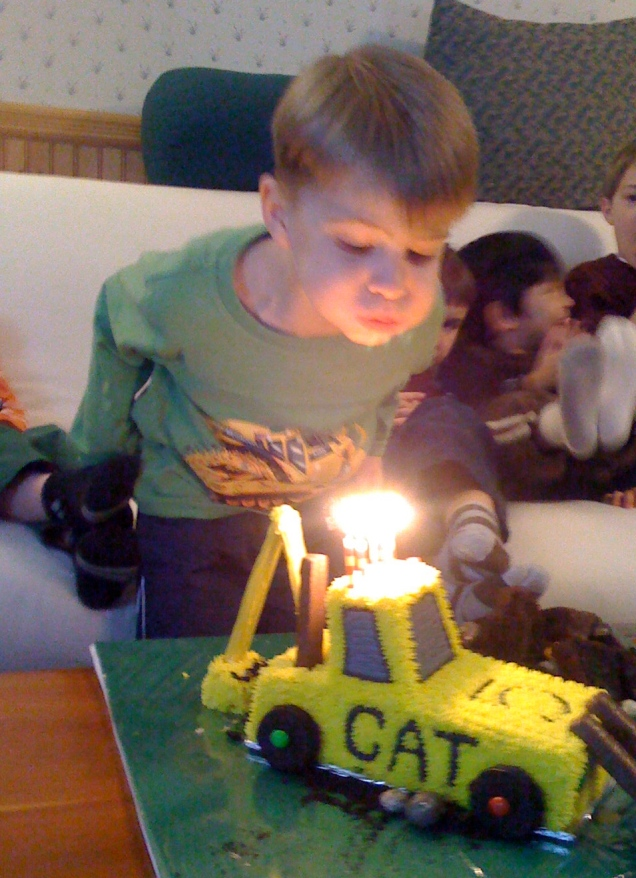 Blowing out the candles on the cake. (Yes, it's a front-end loader cake, and it was even more amazing than it looks in this picture.)