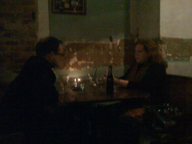 Michael and Jill texting New Years greetings by candlelight at Granville Moore's.