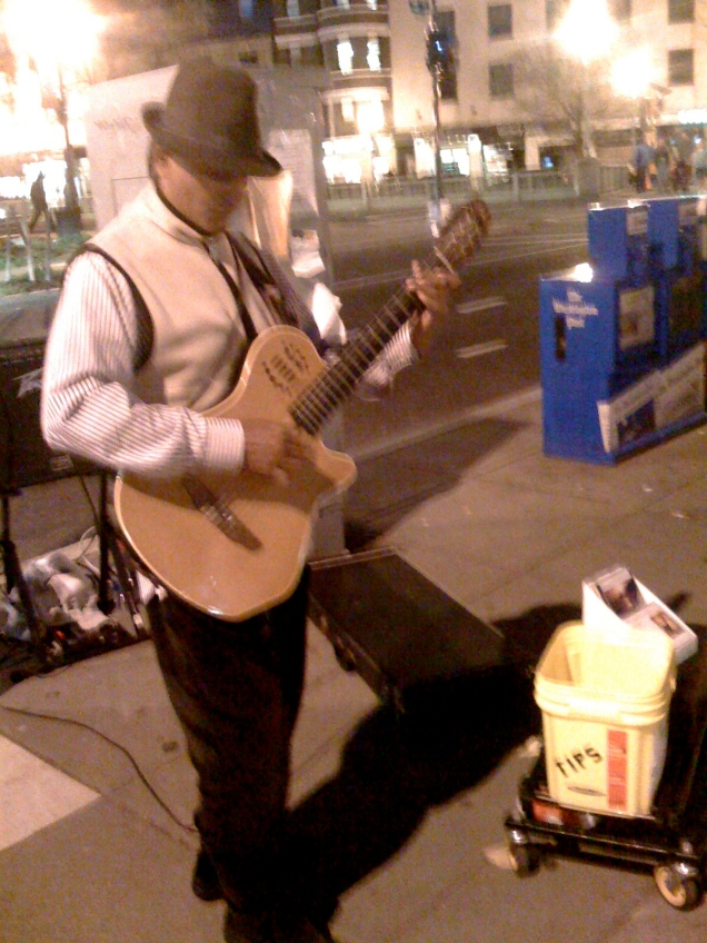 "April 23: This busker is not especially notable, other than the fact that he was playing ""Jingle Bells."" In April."